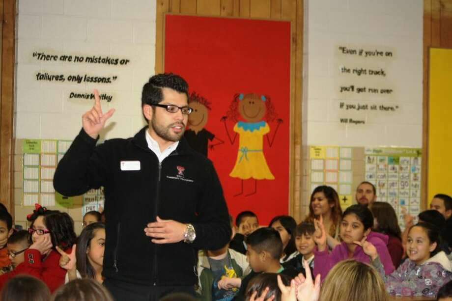"Texas Tech University representative Isaac Flores shows Hillcrest students how to display the ""Guns Up"" hand gesture to demonstrate support for the Red Raiders during a college readiness presentation on Monday."