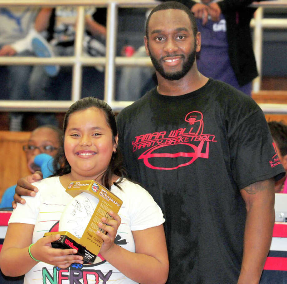 Kevin Lewis/Plainview HeraldFormer Plainview High and Texas Tech star athlete Jamar Wall poses with Edgemere fourth grader Isabel Campos after presenting her with an autographed football. Campos won a poster contest in conjunction with Wall's charity basketball game held Saturday in the DogHouse, which organizer Reggie Williams said raised more than $1,700 for St. Jude's Children's Hospital.