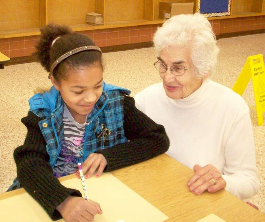 """Courtesy Photo by Linda Milner ShippIn honor of Martin Luther King Day on Monday, the Hale County Literacy Council, RSVP and Wayland students on Friday partnered to present the story of Dr. King to third graders at Edgemere Elementary. Wayland professor Debra Lavender Bratcher read the story with assistance from Wayland students Ebony Holloman, Angelle Miranda and Trishawn Battiste. Each student was able to draw their dream for the future. Lydia Castillo, director of the Hale County Literacy Council, provided a book for each student entitled """"Let's Dream Martin Luther King Jr."""" RSVP volunteers assisting were Inez Hillman, shown here helping student Angel Mora, and Linda Milner Shipp."""
