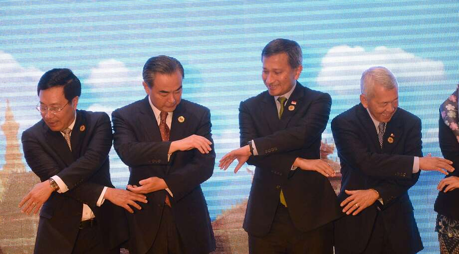 Foreign ministers join hands at their meeting in Vientiane, Laos (from left): Vietnam's Pham Binh Minh, China's Wang Yi, Singapore's Vivian Balakrishnan, and Philippines' Perfecto Yasay. Photo: HOANG DINH NAM, AFP/Getty Images