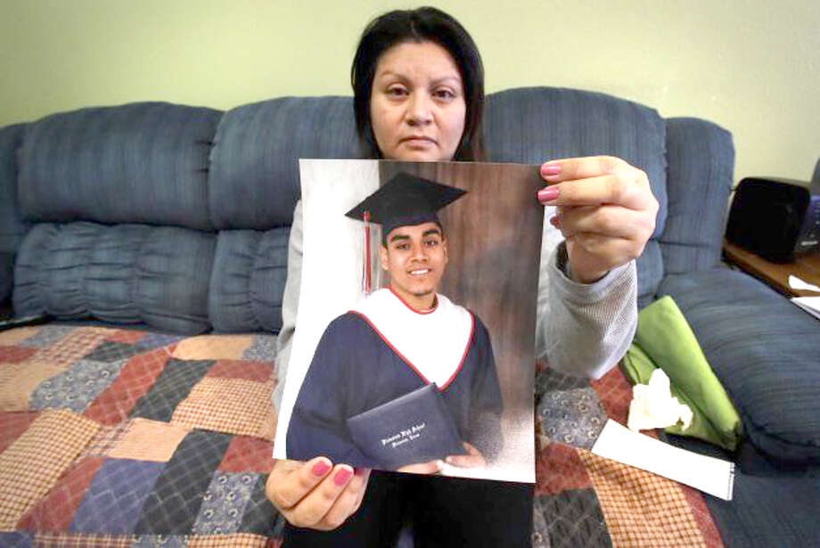 Rachel Enriquez holds a photo of her son Christopher Hinojos, who was gunned down late Tuesday in what San Antonio police describe as a carjacking murder. A 2012 graduate from Plainview High School, Hinojos had just started a new job and was on is way home when the incident occurred. Photo: Bob Owen/San Antonio Express-News