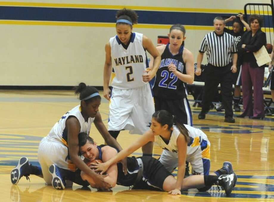 A group of Queens fight for a loose ball against #4 Oklahoma City. From left to right: Christie Mooney and Laura Castillo. Photo: Wayland Baptist University Photo
