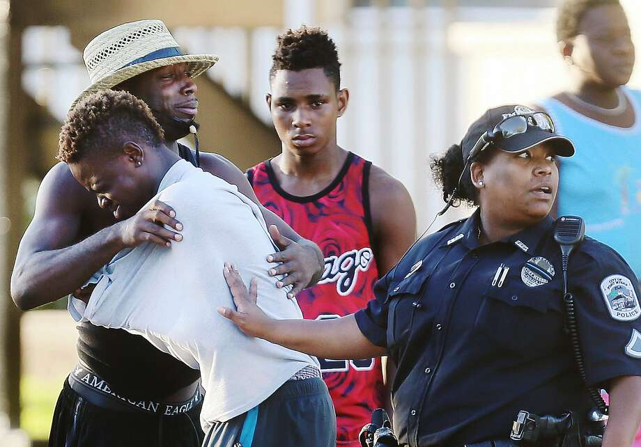 """People embrace after the shooting at Club Blu in Fort Myers, Fla. The club had advertised a beach-themed """"swimsuit glow party,"""" meant primarily for teenagers. Two teens were killed. Photo: Kinfay Moroti, Associated Press"""