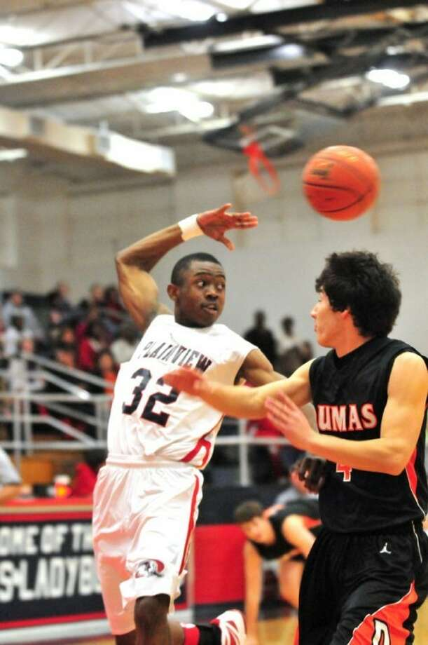 The Plainview Bulldogs' Avysh Hervey (32) throws a pass behind his head as the Dumas Demons' Nathan Thomas defends during a District 3-4A game Tuesday night in the DogHouse. Photo: Ryan Thurman/Plainview Herald