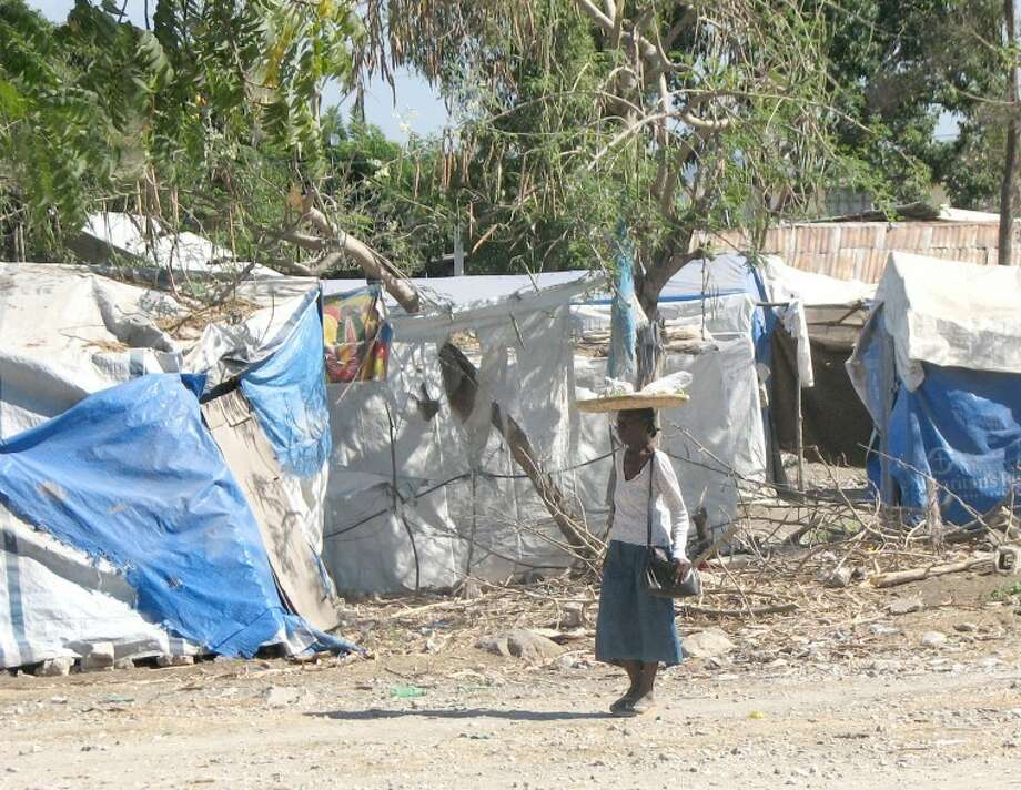 Courtesy PhotoA Haitian woman walks down a street lined with dwellings made from draping tarps over poles. In many instances, this is the closest thing to a home Haitian families have.