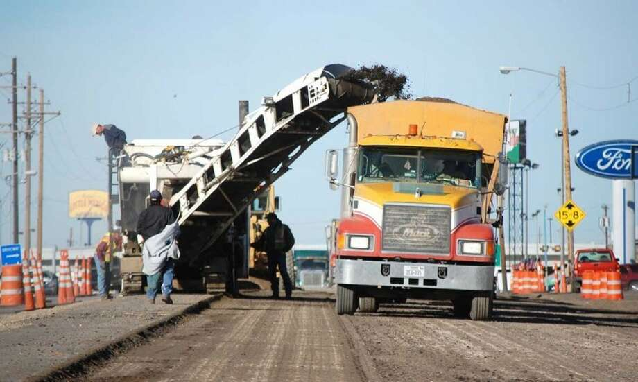 Doug McDonough/Plainview HeraldAfter switching from the south to the north side of U.S. 70 west of Quincy early this week, road construction crews are busy with the process of removing old paving. On Thursday dump truck operators were awaiting their loads of ground asphalt as it was being removed from Olton Road between Ennis Street and I-27. Once the old paving is taken up, construction crews will remove and replace the base material and then add a new layer of asphalt paving. The roadway rebuilding project is moving from west to east, and will involve rebuilding the entire thoroughfare from Westridge Road to Milwee.