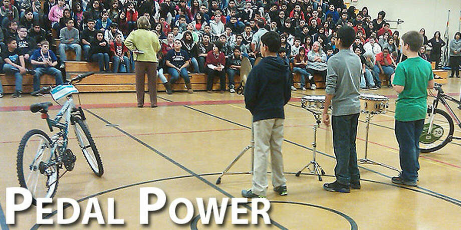 As Coronado Junior High band members Isaiah Garcia, Zach Orozco and Caleb Martin stand by their drums and cymbals, Assistant Principal Carole Sheelar addresses seventh-grade students during a perfect attendance bike presentation Monday. Each six weeks at six local schools, the Plainview Rotary Club presents new bikes or iPods to one boy and one girl who have had perfect attendance.