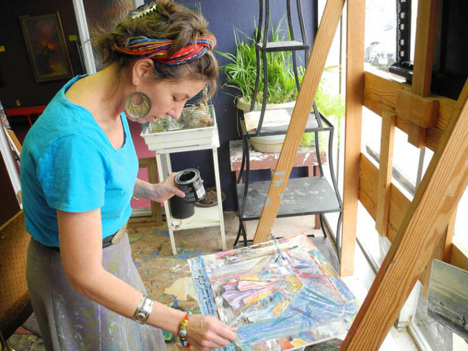 Artist Sally Gubser works to complete a painting using a combination of brush strokes and drip technique. Photo: Gail M. Williams | Plainview Herald