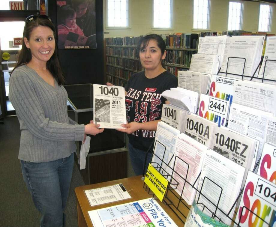 John Sigwald/Unger Memorial LibraryFollowing their delivery Friday, IRS 1040 instruction booklets now are available at Unger Memorial Library. One of the first to pick up a booklet was Chrissy Rogers (left), who received the manual from library aide Regina Lucio. The library now has all of the basic IRS tax forms and instructions available at no charge. Other forms can be printed for 10 cents per page.
