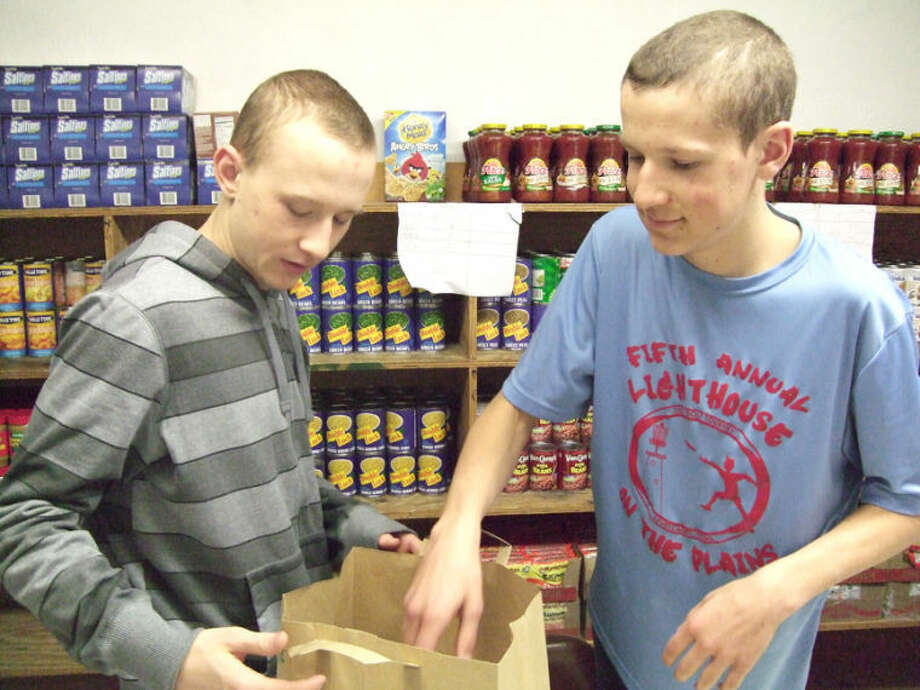 Brothers Travis Heinen, 16 and Joshua Heinen, 14, volunteer at the Faith in Sharing House food bank. Both boys, who are home-schooled, said they, too, are concerned about so many losing their jobs in wake of Cargill's closure. The plant becomes idle Friday. Photo: Shanna Sissom/Plainview Herald