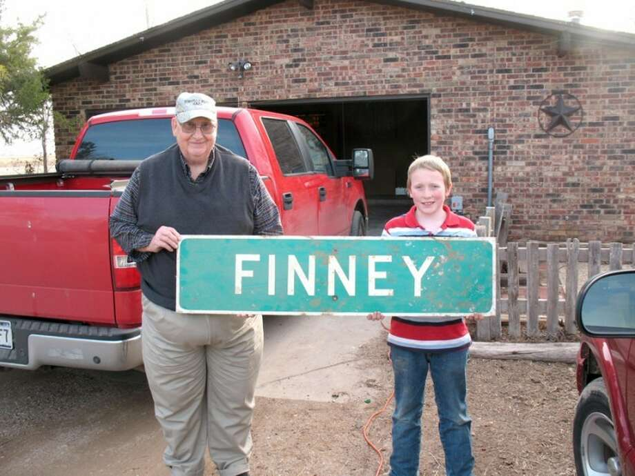 Courtesy PhotoDavid Bye and grandson Cooper hold an old Finney highway sign that was located east across the highway at Finney Switch. TxDOT did not want the sign, so Bye kept it.