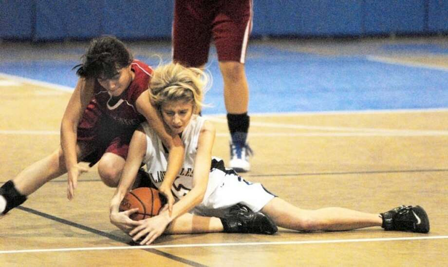 Plainview Christian's Cristen Bothwell (right) goes to the ground to fight for a loose ball against a player from Ascension Academy in a game last week. Photo: Kevin Lewis/Plainview Herald