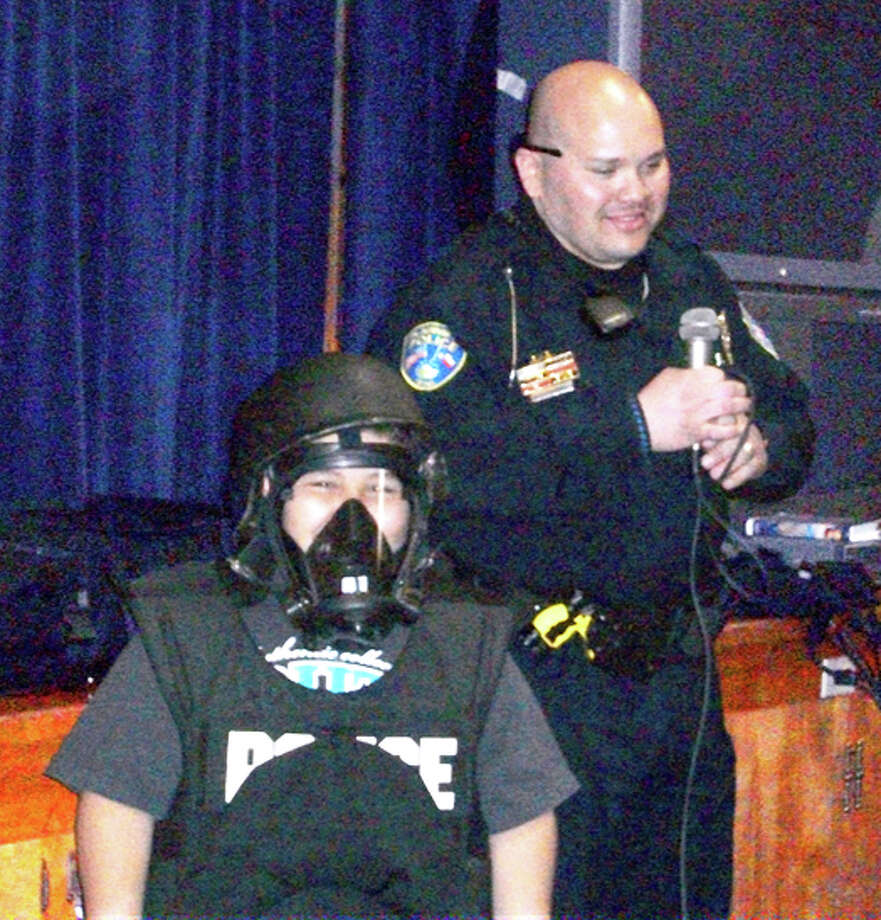 "Courtesy Photo/College HillVictor Vargas (front) tries out SWAT gear during a presentation by Plainview ISD Police Officer Amos Rodriquez for second-grade students at College Hill. The students recently read, ""Officer Buckle and Gloria,"" and Rodriquez was invited to answer students' questions about the duties of a police officer. Second-grade teachers are Jennifer Havens, Linda Ray and Kelly Mendoza."