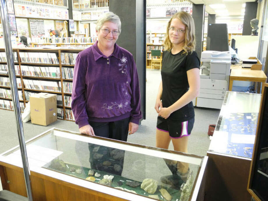 Dixie Cox and daughter Katie stand behind one of the society's display cases at Unger Memorial Library. The Cox family has been rock collecting for about 16 years. Photo: Gail M. Williams | Plainview Herald