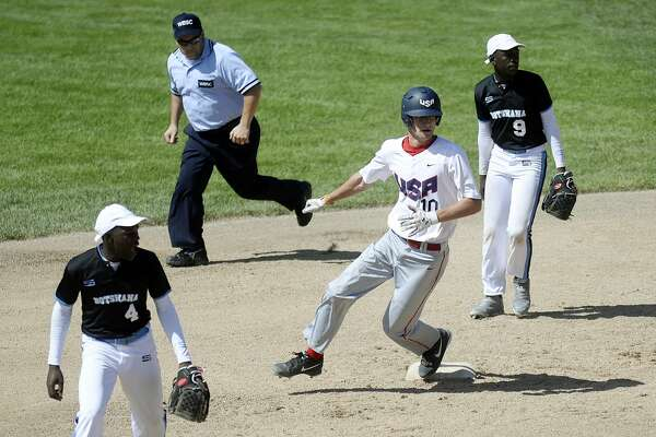 Team USA's Jeff Lewis, center, rounds second base as Botswana's Kabo Kealotswe, left, and Maatla Mpeba look on during the fourth inning on Monday at Currie Stadium. Team USA beat Botswana 14-0.