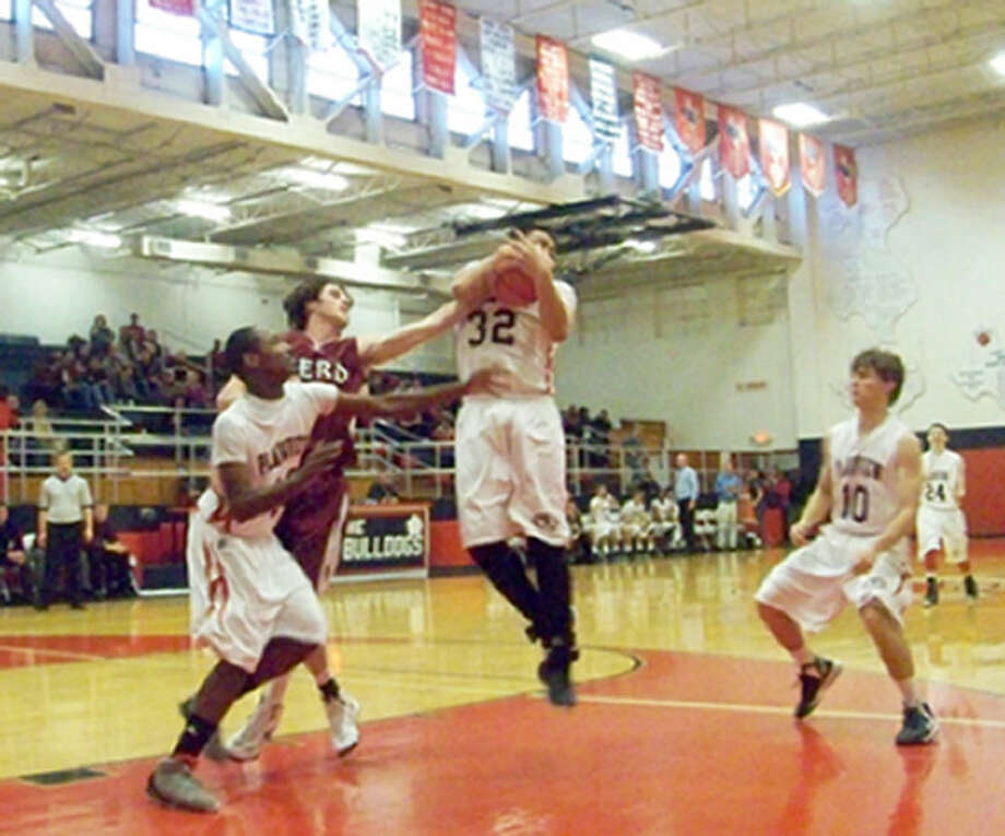 Bulldog Joby Muniz pulls down a rebound during Tuesday's contest with Hereford. Photo: Jessica Thornton/Plainview Herald
