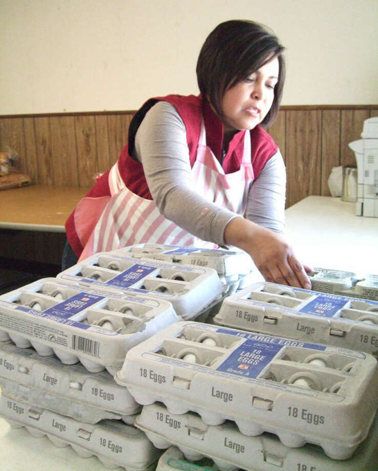 "Salvation Army Capt. Adriana Martinez arranges groceries from Wednesday's shipment from the High Plains Food Bank. New families, most ""first-timers,"" have sought food assistance since Cargill's closure, the Salvation Army reports. Photo: Shanna Sissom/Plainview Herald"