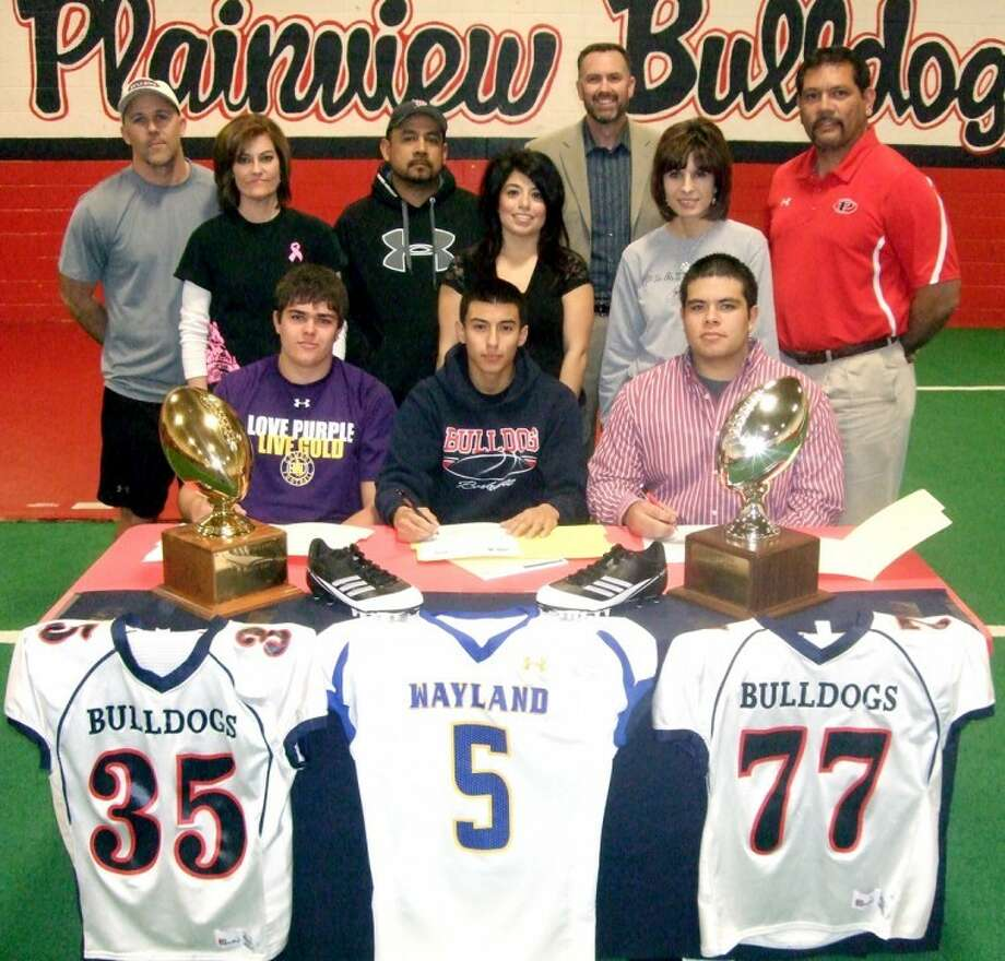 Plainview Bulldogs Trent Walker (seated, left), Chris Salazar and Marcos Hinojos Jr. on Wednesday signed letters of intent to play football at Hardin-Simmons, Wayland and Eastern New Mexico, respectively. Also pictured are their parents, Lee and Sonia Walker, David and Tiffany Amador and Marcos and Jessica Hinojos, as well as PHS Principal Tye Rogers (third from right.) Photo: Kevin Lewis/Plainview Herald