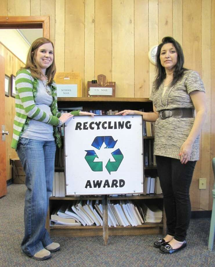 Courtesy Photo by Sherri CheyneCassidy Gibbs (left) and Sylvia Hinojos display the Recycling Award sign that Houston School will display this month after being recognized by Pitch In Plainview. The school was honored for its efforts in reducing waste by sorting trash and sending paper to the recycling center.