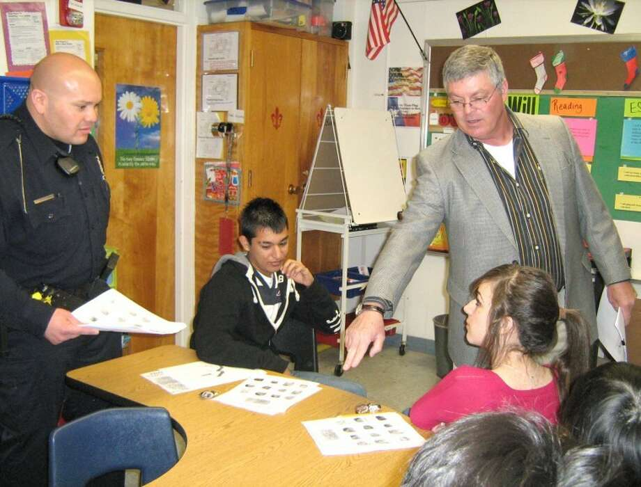 Crystal Burdis/Plainview High SchoolPlainview ISD School Resource Officer Amos Rodriguez (left) and Sgt. Stan Branam of the Plainview Police Department recently presented a lesson on fingerprint identification to students, including Yonatan Hernandez and Brenda Martinez, in Crystal Burdis' ESL classroom at Plainview High School. The students have been reading about crime scene science, so Burdis invited the officers to speak to the class.