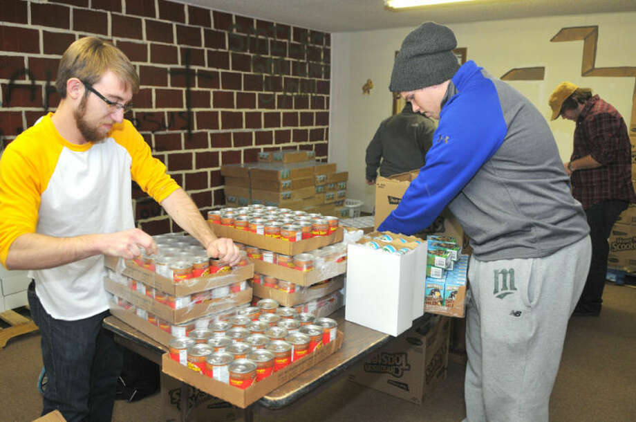Wayland freshman Zaca Wilson (left) is joined by junior Matt Evans as they get food ready to put in backpacks for Thunderbird School students. Photo: Richard Porter/Wayland Baptist University