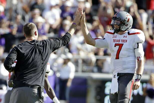 Texas Tech head coach Kliff Kingsbury, left, celebrates with quarterback Davis Webb (7) after a touchdown against TCU in the first half of an NCAA college football game, Saturday, Oct. 25, 2014, in Fort Worth, Texas. (AP Photo/Tony Gutierrez)