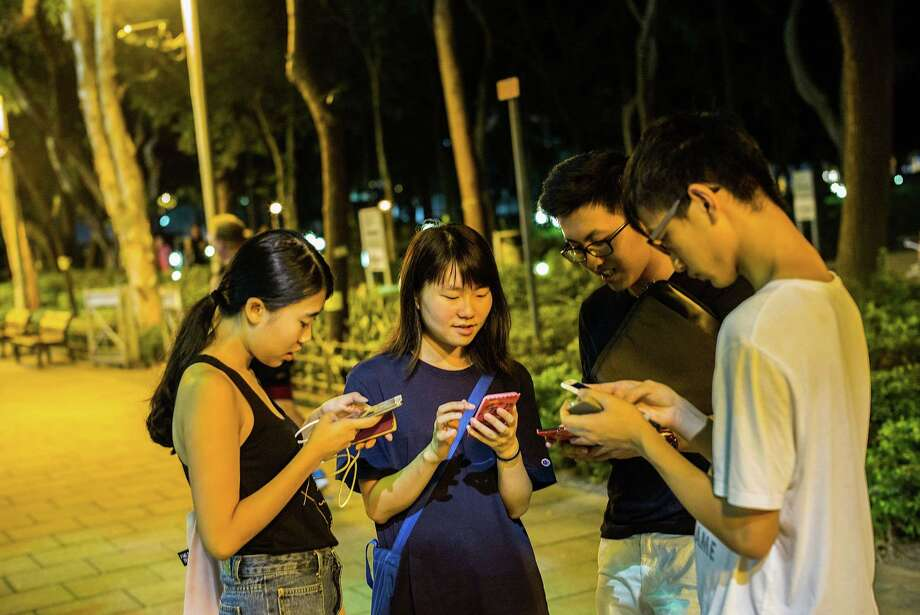 """People play the """"Pokémon Go"""" game Monday in Tsim Sha Tsui, Hong Kong. Since its global launch, the mobile game has been an unexpected megahit among users who have taken to the streets with their smartphones. But Nintendo Co. shares plunged by the most since 1990 in Monday trading. Photo: Lam Yik Fei /Getty Images / 2016 Getty Images"""
