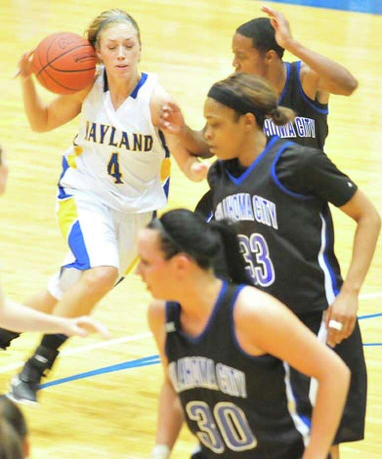 Wayland senior Erika Raymond (4) of Plainview briefly loses control of the ball as she drives to the basket against OCU. Photo: Kevin Lewis/Plainview Herald