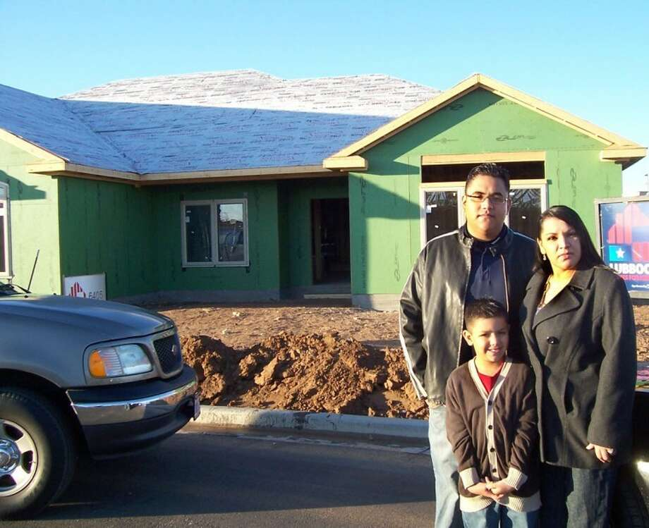 Doug McDonough/Plainview HeraldRetired Army medic Louis Flores Jr., his wife Olga and their son Gabriel stand in front of their future home in Southwest Lubbock. A 2002 Plainview High graduate, Flores is this year's recipient of the Lubbock Homes for Heroes project.