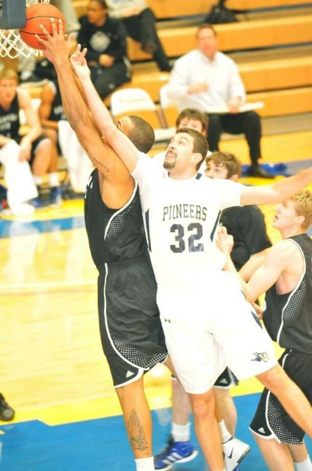 Wayland's Johnny Terra reaches for a rebound against OCU. Photo: By Kevin Lewis