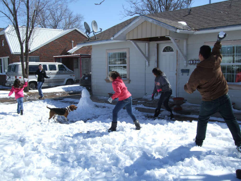 Ivan Monarrez (far left) keeps his distance during a snow fight with his family, Fatima (left), Valerie and Elizabeth Monarrez, as Joey Martinez joins in. Photo: Shanna Sissom/Plainview Herald