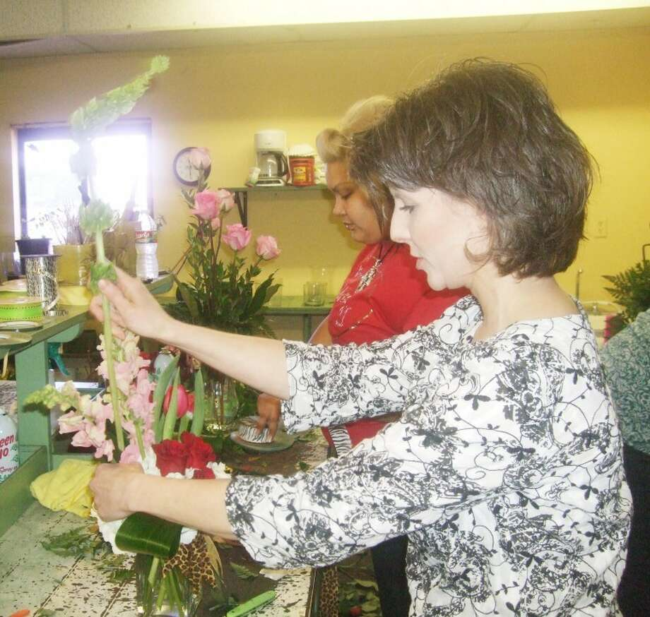 Jessica Thornton/Plainview HeraldPetals owner Tiffany Barnes (front) and employee Laura Medina prepare floral arrangements for delivery Tuesday. Barnes said the most popular Valentine's Day flower choice was a dozen red roses followed by a mixed arrangement of red, pink and white flowers.