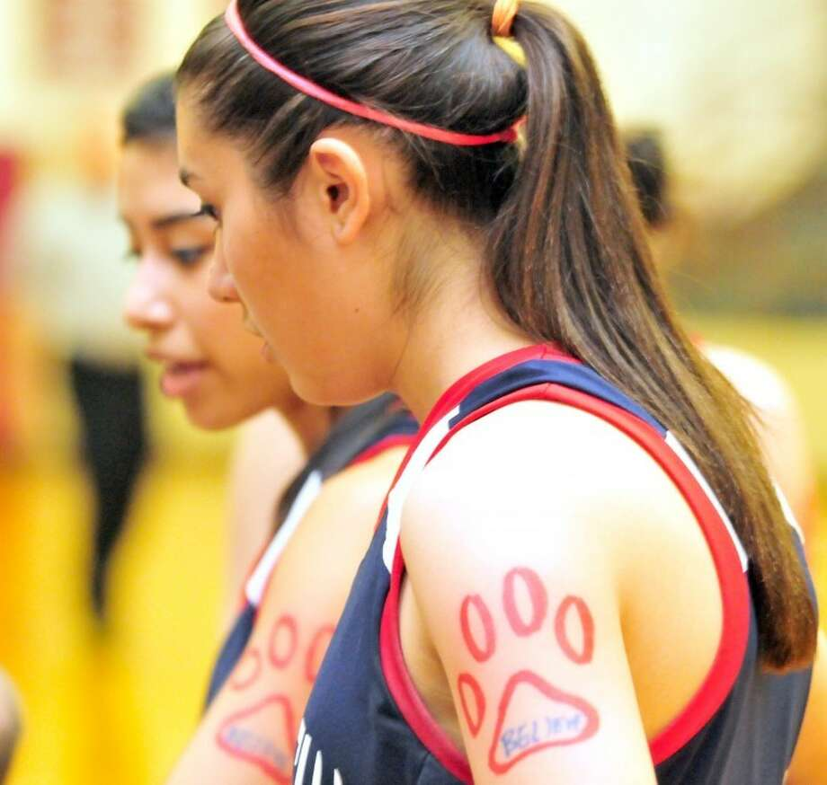"Plainview Lady Bulldog Lizette Ramirez, sporting a traditional paw print playoff tattoo featuring ""BELIEVE"", listens during a timeout at Monday night's bi-district game against Wichita Falls Rider in Vernon. No. 21 Plainview won 61-51 in overtime to advance to an area round game, likely against unbeaten and sixth-ranked El Paso Chapin, tentatively set for 7:30 p.m. Friday at Odessa College."