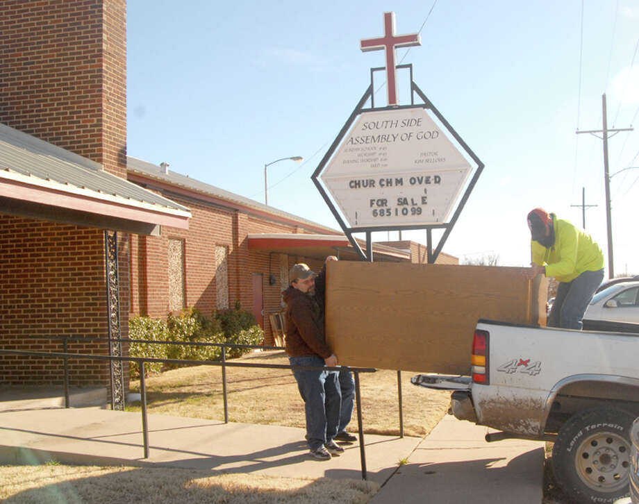 Kevin Lambright (left) and Jessie Lambright help Gary Tipton load a desk Saturday at a church garage sale in the former Southside Assembly of God building. Following the merger of Southside with Glad Tidings Assembly, the new congregation is meeting at 301 S.E. Ninth while using Southside for its food pantry. That building is now in contract to be sold, and the congregation is selling pews, two pianos, an organ, furniture, books, hymnals and related items. Interested individuals should contact Bellows at 806-685-1099.
