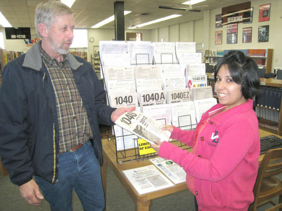 Unger Library patron Paul Cothran gets a tax form Tuesday from library aide Liz Flores. Following multiple delays, the IRS 1040 instructions and other forms are now available at the library. Photo: John Sigwald/Courtesy Photo