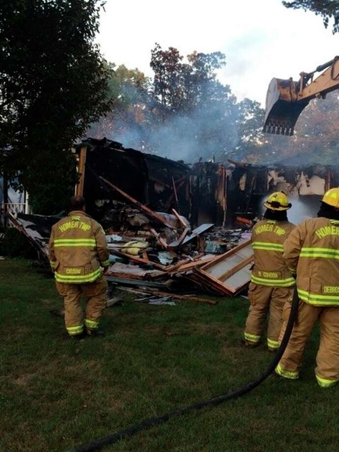 Firefighters at the scene of the July 19 fire that destroyed the home at 993 S. 10 1/2 Mile Road, in Lee Township.