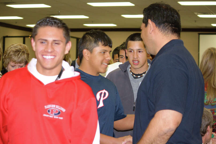 Marcos Hinojos (right) is congratulated by PHS athletes Pablo Jimenez, Nathan Leyendecker and Jose Arvizu after Hinojos' contract as athletic director and head football coach was extended for one year at Thursday night's school board meeting. (See story Page 1B.) Photo: Jan Seago/Plainview ISD
