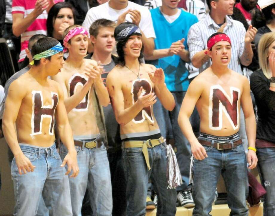 "Tulia fans Johnny Padilla (left), Troy White, Alex Deverte and Jair Macias spell the first four letters of ""Hornets"" on their painted chests during last week's Class 2A area round playoff game against Slaton in Hutcherson Center. The Lady Hornets play there again tonight."