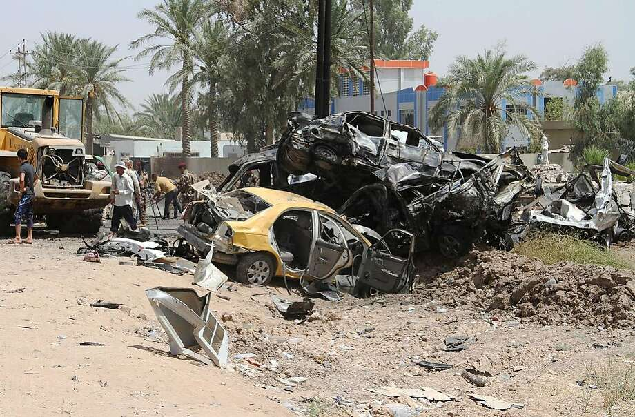 Iraqis examine damage at the site of a suicide bomb attack at the entrance to the town of Khalis. Photo: YOUNIS AL-BAYATI, AFP/Getty Images