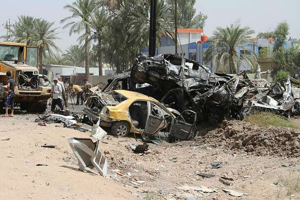 Iraqis inspect the damage at the site of a suicide bomb attack at the entrance to the town of Khales, 80 kms northeast of Baghdad, on July 25, 2016. A suicide bomber detonated an explosives-rigged vehicle near a checkpoint at the entrance to the town of Khales killing 10 people and wounding 36 people, officials said.  / AFP PHOTO / YOUNIS AL-BAYATIYOUNIS AL-BAYATI/AFP/Getty Images
