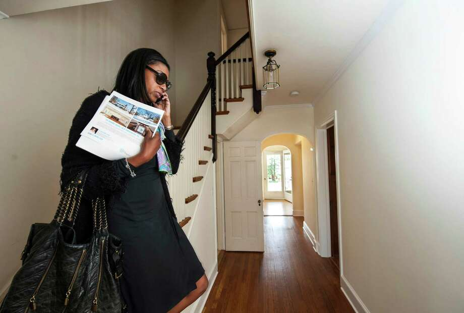 Carolyn Gould a real estate agent from Long Island, N.Y., walks through a house in Old Greenwich as part of a bus tour put together by Douglas Elliman Real Estate last year. Second-quarter home sales in Fairfield County reached their highest level in a decade, according to a new report from Elliman. Photo: Mark Conrad / Hearst Connecticut Media / Connecticut Post Freelance