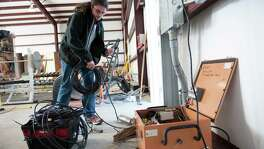 Remi Oldham, an SMU geophysics graduate student, runs a cable to connect the seismometer to communications interface equipment housed in the orange metal box in Willow Park. Details of the Southern Methodist University study are in this month's Physics of the Earth and Planetary Interiors journal.