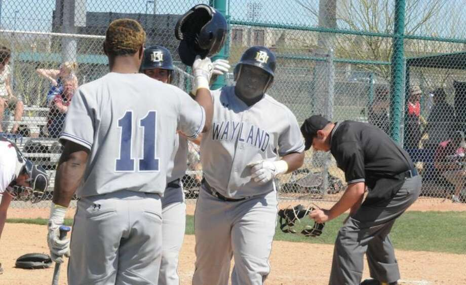 Wayland's Mark Davis is greeted at the plate by Gabriel De La Cruz (11) after Davis hit his second home run of the season in Wednesday afternoon's 16-7 win over Valley City State (N.D.) at the Tucson Invitational. Photo: Calvin Bass/Wayland Baptist University
