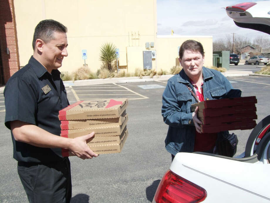 Pizza Hut General Manager Mike Mendoza helps Faith in Sharing House volunteer Suzanne Gill load her car with pizza left over from Tuesday's lunch buffet. The restaurant has partnered with FISH to help feed families in need. Photo: Shanna Sissom/Plainview Herald