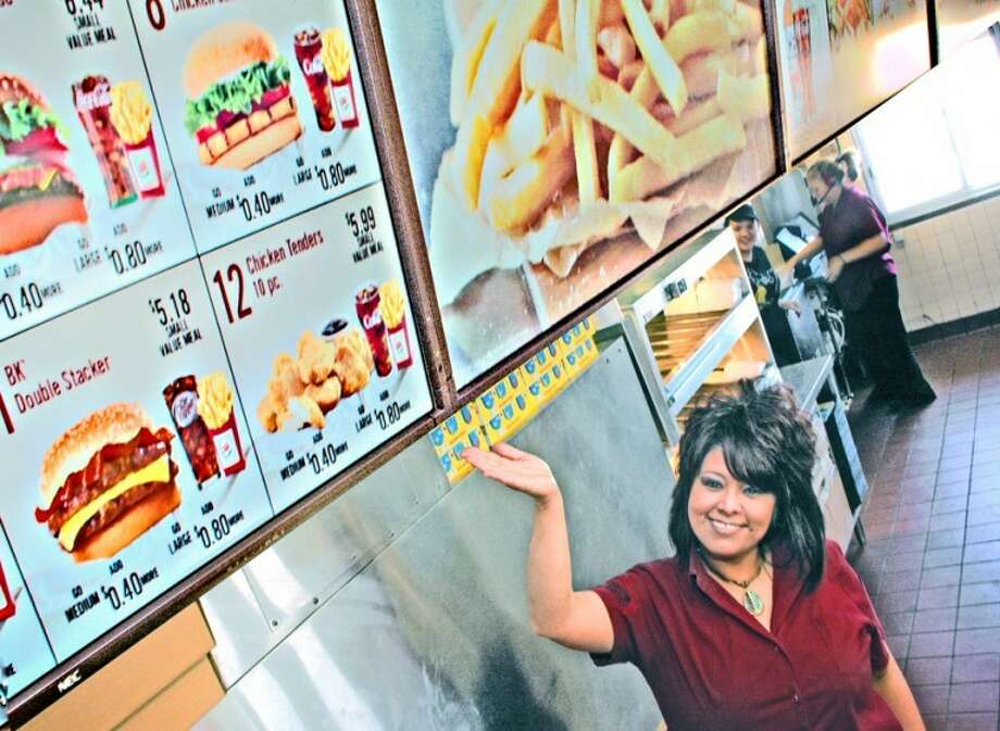 Gordon Zeigler/Plainview Herald  JoAnn Longoria shows off new high tech menu board at Plainview Burger King, 1003 Interstate 27, which shows customers the latest BK food illustrations and pricing. The panoramic display updates as often as every 15 minutes, if needed, thanks to the Internet. It switches automatically from breakfast to the regular BK menu and includes full video display of popular menu items and specials. Owner David Isaacson, who has operated Burger King since 1987, said the automated system with bright LCD monitors went up Wednesday.