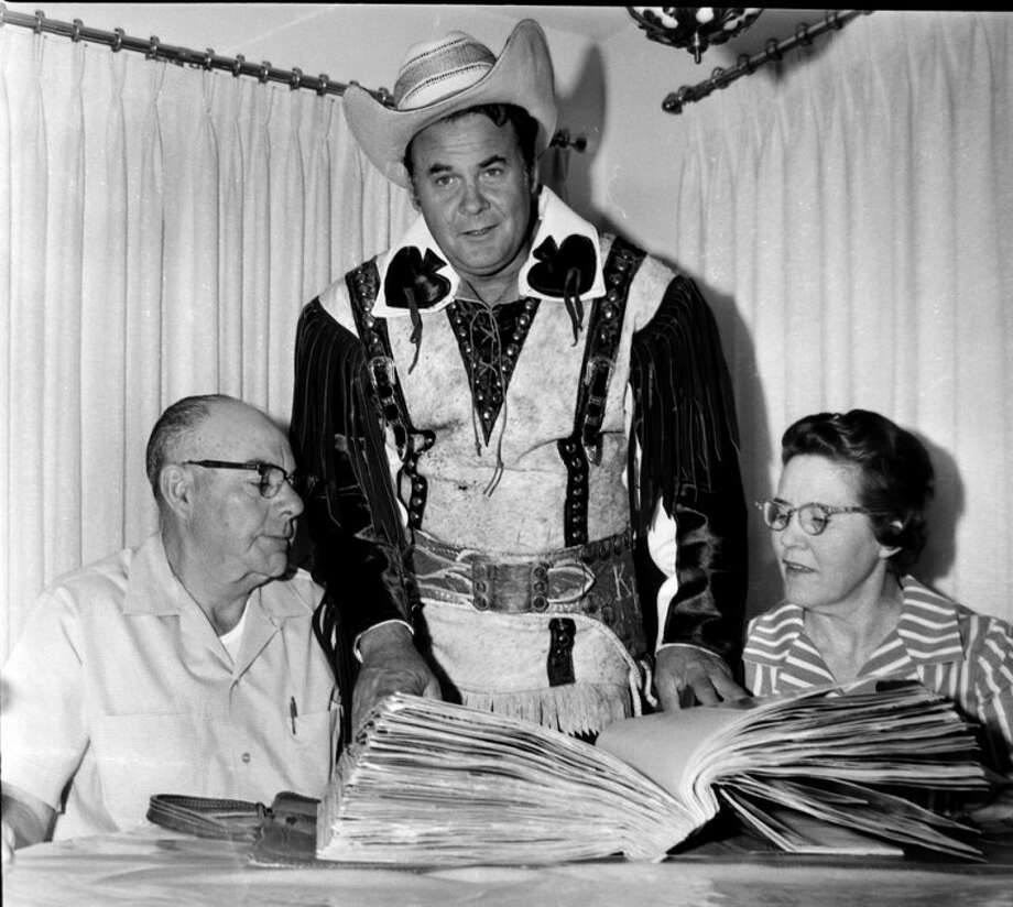 "Herald File PhotoFormer Western film star Sunset ""Kit"" Carson shows a bulging scrapbook filled with press clippings to Thrane and Imogene Parsons during a 1967 visit to Plainview following a 10-year world tour."