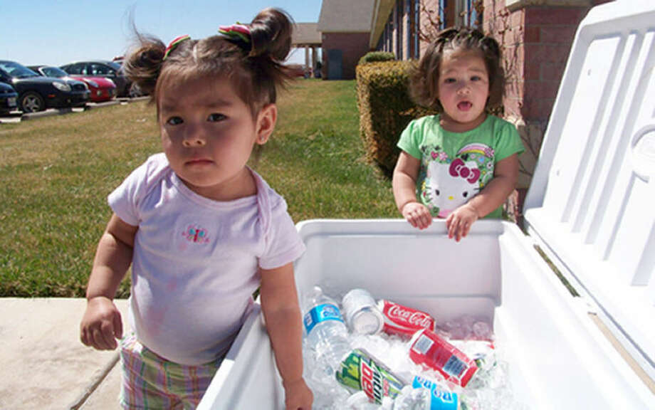 Portia Luna (left) and Khloe Ybarra gather around an ice chest filled with an assortment of drinks during Prairie House Living Center's St. Patrick's Day celebration.