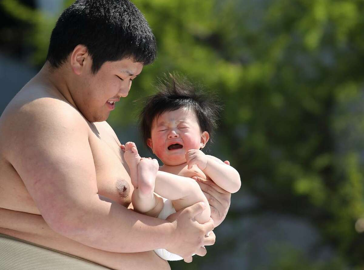 TOKYO - APRIL 25: A crying baby is carried by Sumo wrestling student during the Crying Sumo competition at Sensoji Temple on April 25, 2010 in Tokyo, Japan. The first baby to cry wins the competition. The ceremony takes place in Japan to wish for the good health of the child as it is said that crying is good for the health of babies. (Photo by Koichi Kamoshida/Getty Images)