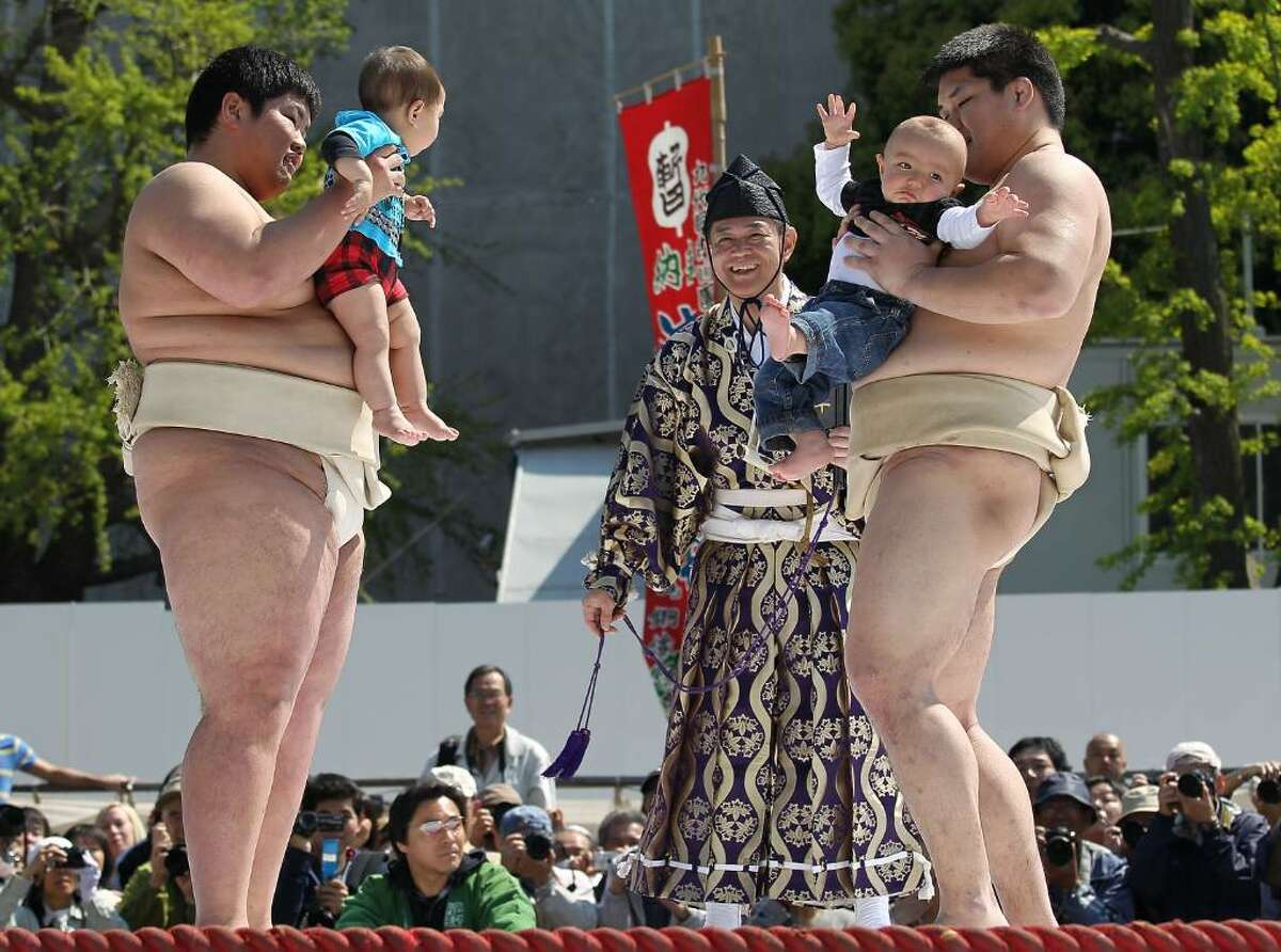 TOKYO - APRIL 25: Sumo wrestling students hold babies as they try to make them cry during the Crying Sumo competition at Sensoji Temple on April 25, 2010 in Tokyo, Japan. The first baby to cry wins the competition. The ceremony takes place in Japan to wish for the good health of the child as it is said that crying is good for the health of babies. (Photo by Koichi Kamoshida/Getty Images)