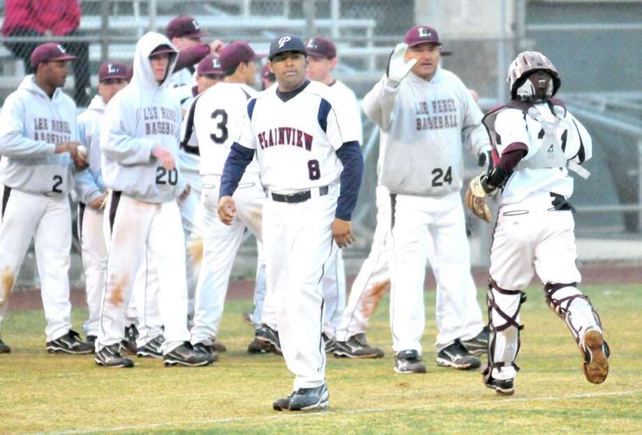 Plainview baseball coach Hector Limon Jr. (8) heads back to the Bulldog dugout while his father, Midland Lee coach Hector Limon (24), greets his playes as they run off the field during Monday's game at Bulldog Park. Limon Sr. previously coached at Plainview. Photo: Kevin Lewis/Plainview Herald